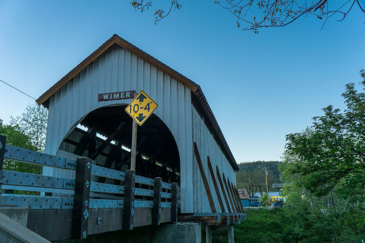 Architecture Building Exterior Built Structure Clear Sky Communication Covered Bridge Day Guidance Low Angle View No People Oregon Outdoors Road Sign Sky Text Tree Wimer Wimer Covered Bridge Yellow