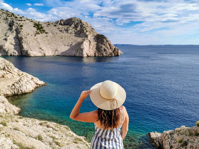 Woman standing on rocky shore, admiring the view, sea, summer, one person, hat.