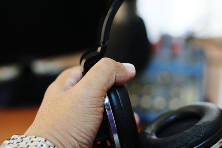 Close-up of hand holding headphones