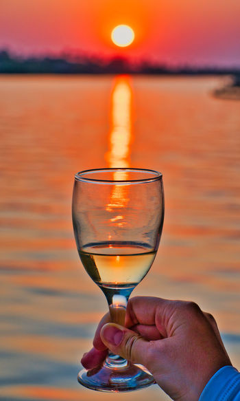 Midsection of person holding wineglass against orange sky during sunset