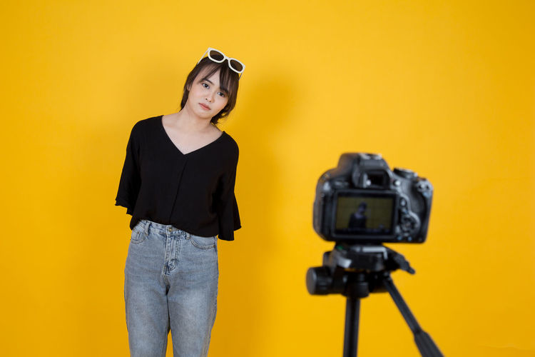 Vlogger making video while standing against yellow background