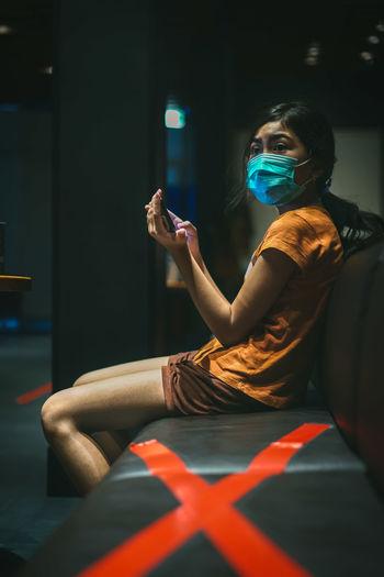 Girl wearing mask looking away while using phone