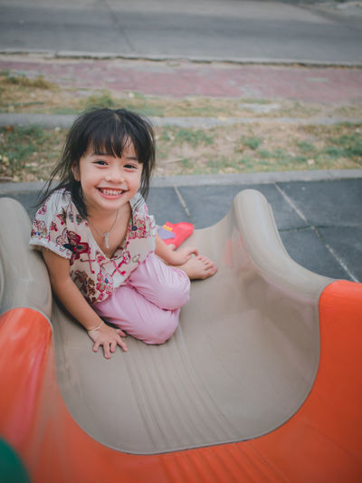 Cute little asian girl smile on playground Smiling Childhood One Person Looking At Camera Child Girls Portrait Real People Sitting Females Happiness Women Casual Clothing Innocence Emotion Front View Lifestyles Full Length Cute Outdoors Hairstyle Bangs Day