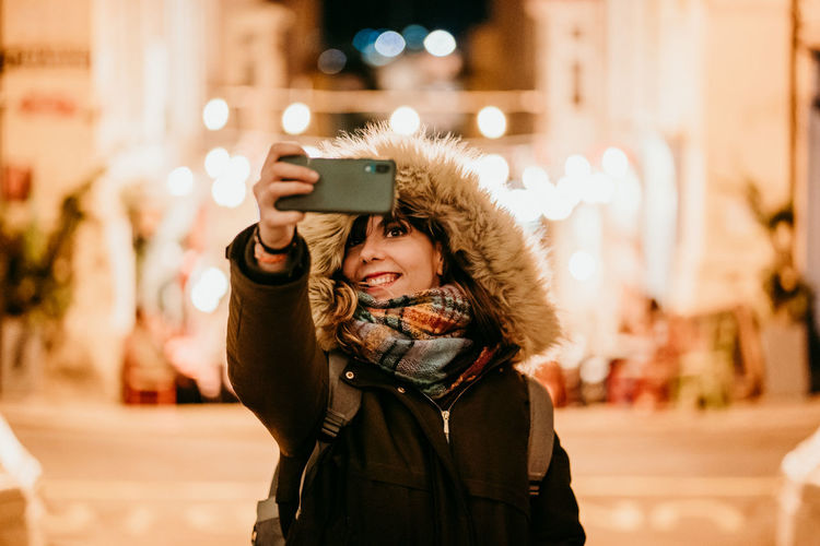 Portrait of smiling young woman using smart phone in winter