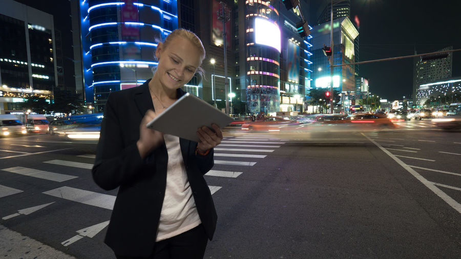 Young woman using touch pad on the busy street of night Seoul city in Republic of Korea. Illuminated buildings, motorway with car traffic and pedestrian crossing in background ASIA Business Car Cars City City Life City Street Computer Illuminated Lifestyle Night One Person Only Men People Person Seoul South Korea Street Tablet Technology Touchpad Wireless