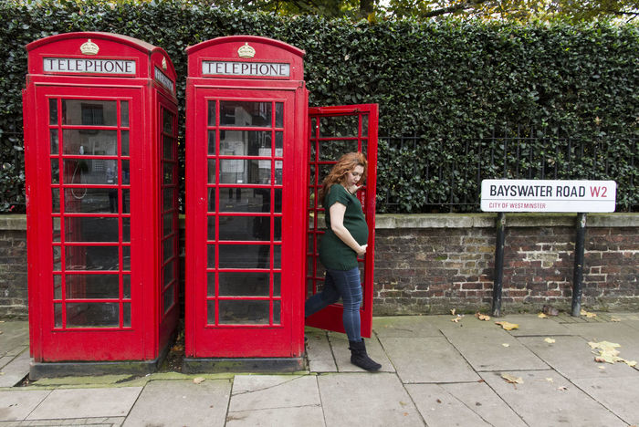 Red Text Communication Day Outdoors London Lifestyle Pregnant Pregnancy Adult Warm Clothing Long Hair Casual Clothing One Woman Only Red Pay Phone Telephone Real People.Telephone Booth Architecture Horizontal