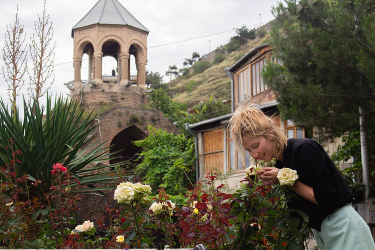 Young Woman Smelling Flowers In City