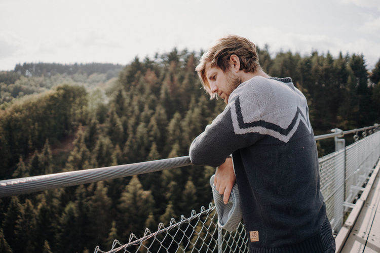 Man looking down from hanging bridge One Person Railing Real People Lifestyles Leisure Activity Tree Standing Side View Day Adult Three Quarter Length Nature Focus On Foreground Mature Adult Plant Women Short Hair Casual Clothing Warm Clothing Outdoors Hair Hairstyle Footbridge Hanging Bridge Forest Holiday Moments