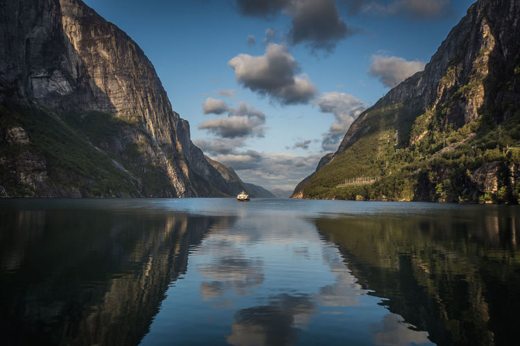 Scenic view of fjord and mountains against sky