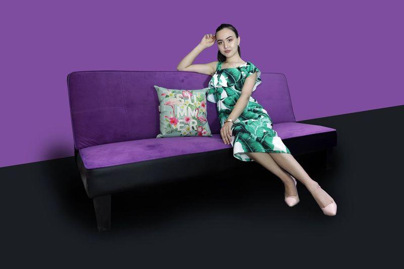 Portrait of woman sitting on sofa against purple wall