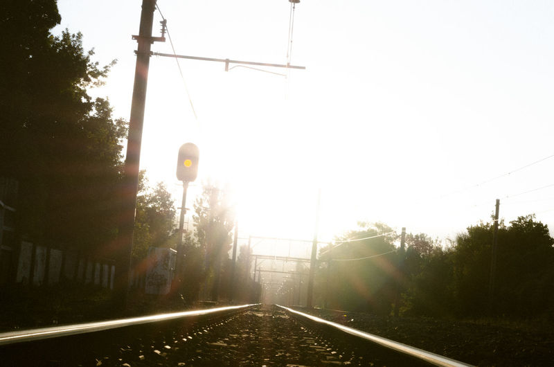 View of railway tracks and trees against clear sky