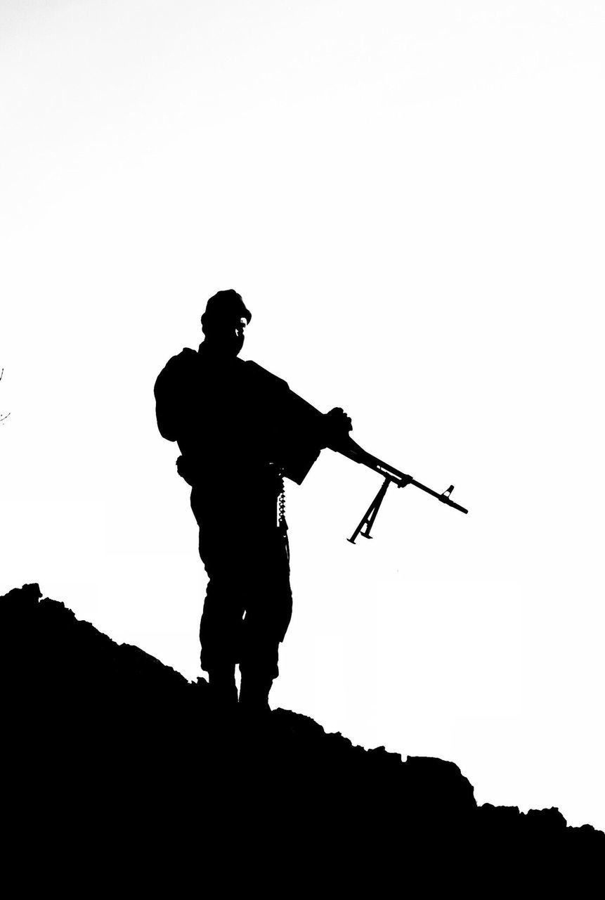 silhouette, full length, copy space, standing, low angle view, clear sky, outdoors, men, holding, real people, army soldier, one person, day, occupation, sky, nature, only men, people