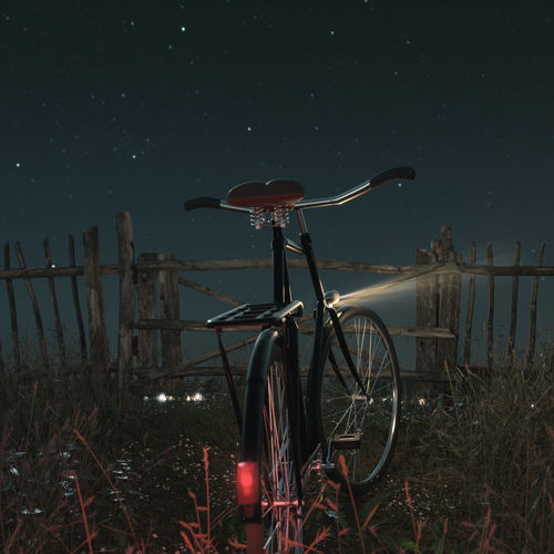 Bicycle by fence on field against sky at night