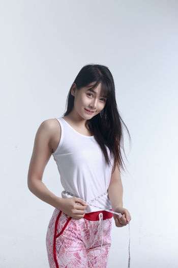 Woman measuring waist against white background