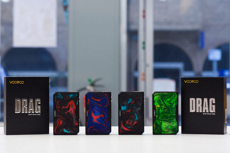 The Voopoo Drag 2 vape kit Multi Colored Focus On Foreground No People Close-up In A Row Variation Group Of Objects Green Color Choice Indoors  Container Side By Side Day Still Life Communication Text Order Retail  Art And Craft Voopoo Dragonfly Vape Modern