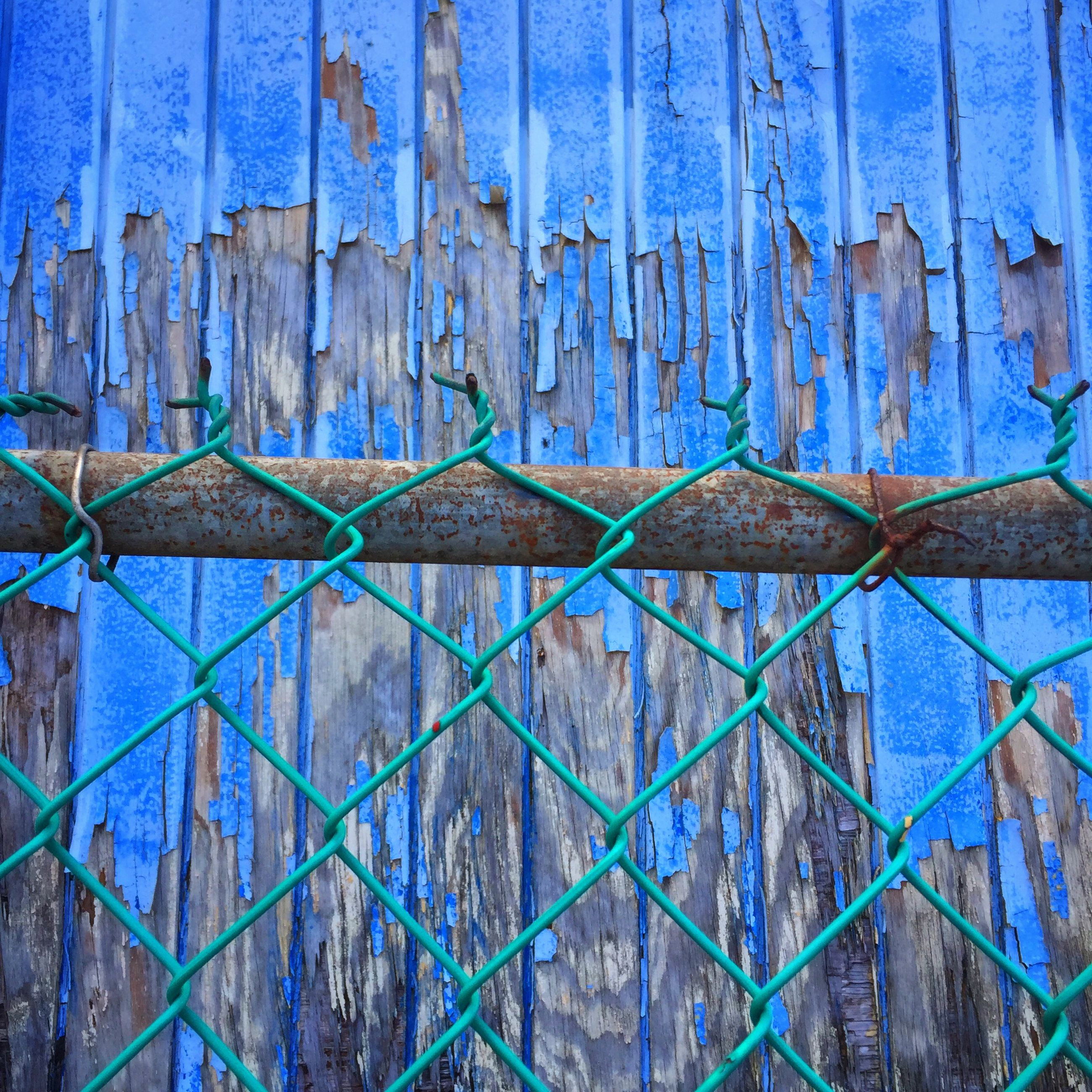 full frame, backgrounds, blue, metal, protection, built structure, pattern, safety, architecture, textured, wall - building feature, close-up, security, weathered, fence, closed, rusty, building exterior, metallic, old