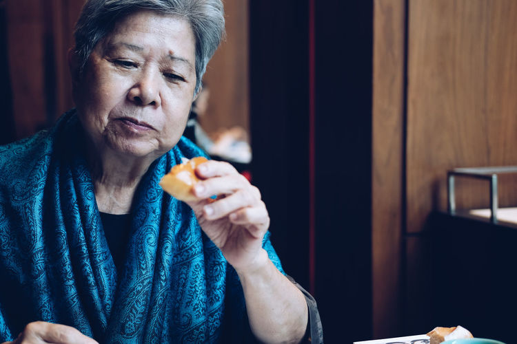Senior woman eating breakfast at home