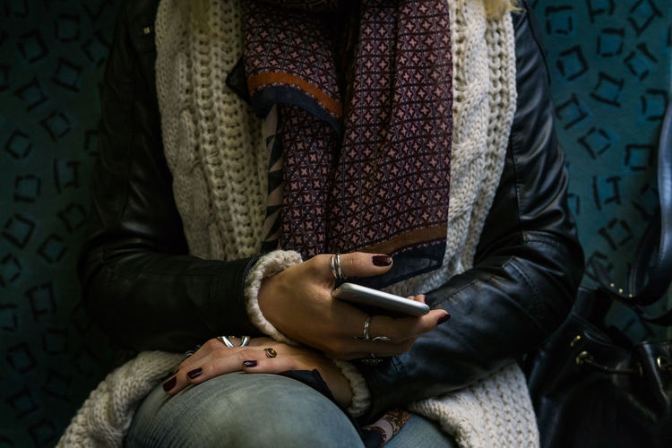 Midsection Of Woman Holding Mobile Phone In Train