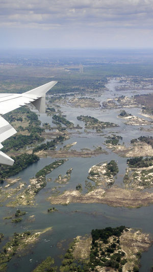 View of the Zambesi River landing at Livingstone Airport in Zambia. Livingstone  View Zambia Aerial View Aircraft Wing Airplane Beauty In Nature Cloud - Sky Day Flying Journey Landing - Touching Down Landscape Nature No People Outdoors River Scenics Sky Tranquility Transportation Travel Travel Destinations Water Zambezi
