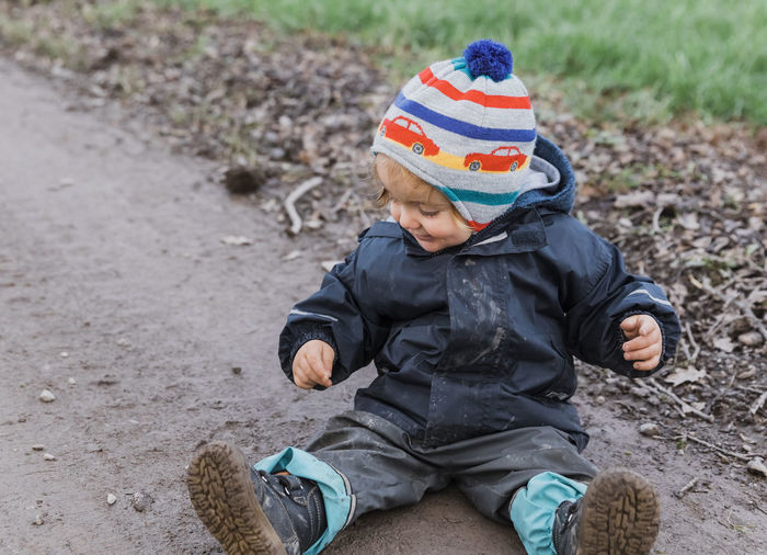 Happy toddler girl sitting with muddy pants on dirt road - Kempen, Germany Adventure Baby Boot Carefree Casual Caucasian Cheerful Child Childhood Close-up Coat Curiosity Cute Dirt Dirty Excitement Exploring Field Footpath Front View Full Length Fun Germany Girl Hand Happy Innocence Jacket Joy Land Looking Down Messy Mud Nature One Outdoors Pants People Playing Pointing Portrait Raincoat Road Sitting Smiling Toddler  Unhygienic Weather Wet Winter Boys Males  Young Day One Person Real People Clothing Babyhood Knit Hat Leisure Activity Three Quarter Length Warm Clothing
