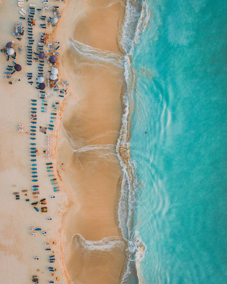 An aerial view of Jolly Beach at dusk with small beach umbrellas and chairs dotting the sand as the blue waves crash on the beach for a perfect contrast. Shot in Antigua and Barbuda in the Caribbean. See more: Instagram.com/LostBoyMemoirs & LostBoyMemoirs.com Aerial Shot Caribbean Sea DJI X Eyeem Drone  EyeEm Best Shots From Above  Island Life Island View  Print The Week on EyeEm Beach Birds Eye View Dji Dji Phantom Drone Photography Dronephotography Island Nature Sea Seaside Turquoise Water Vacation Wallpaper Water Waves