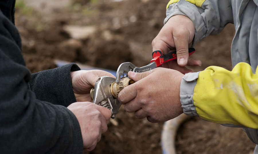 instalation a water supply in a new house Construction Site Home Industry Water Supply Worker Building Close-up Day Dirty Fittings Handyman Holding Hose House Human Hand Instalations Pipe Pliers Real People Soil Two