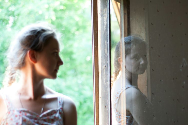 Woman looking away by window at home