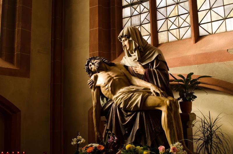 Statues of john the baptist holding jesus christ in church