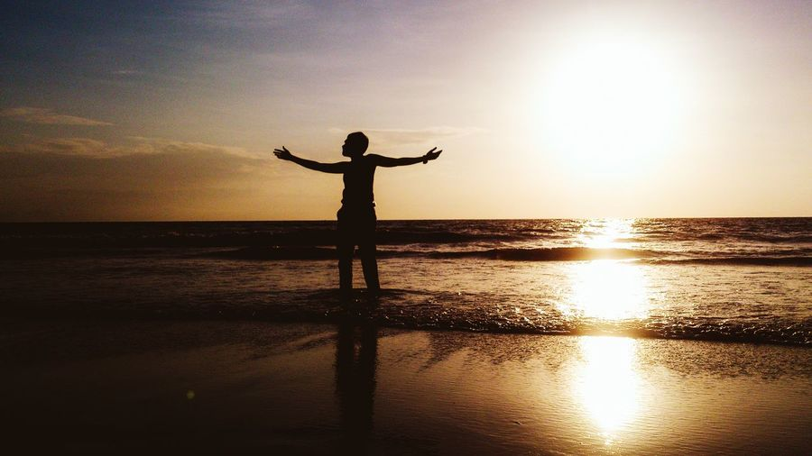 Silhouette man standing with arms outstretched on shore at juhu beach during sunset