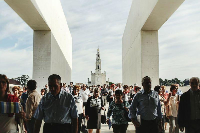 People standing in front of golden gate bridge against sky