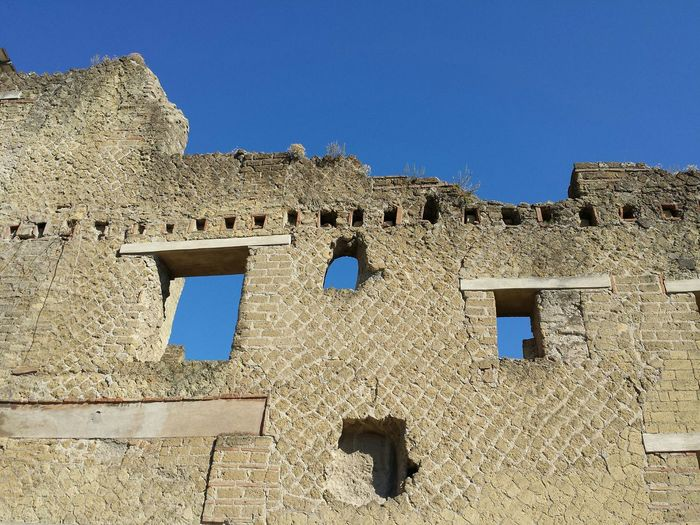 Low angle view of old wall against clear sky