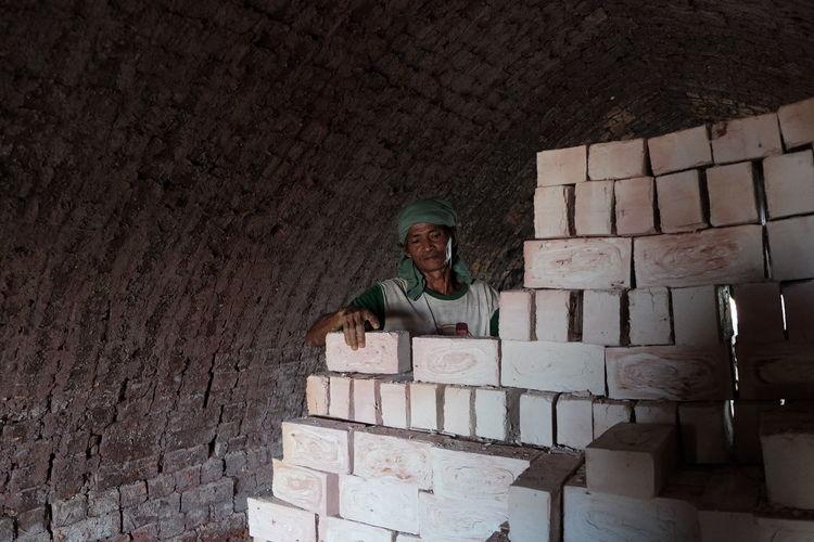 Man Arranging Bricks In Tunnel