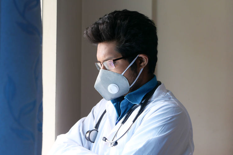 Close-up of doctor wearing mask standing by window