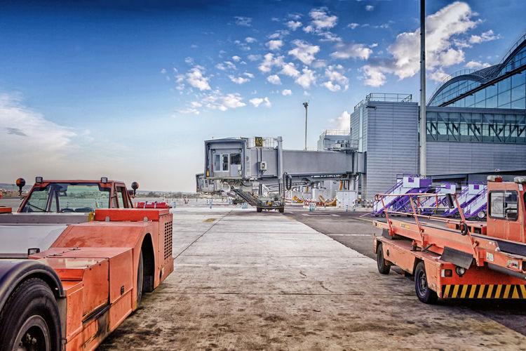 Passenger boarding bridge and vehicles on airport runway against sky