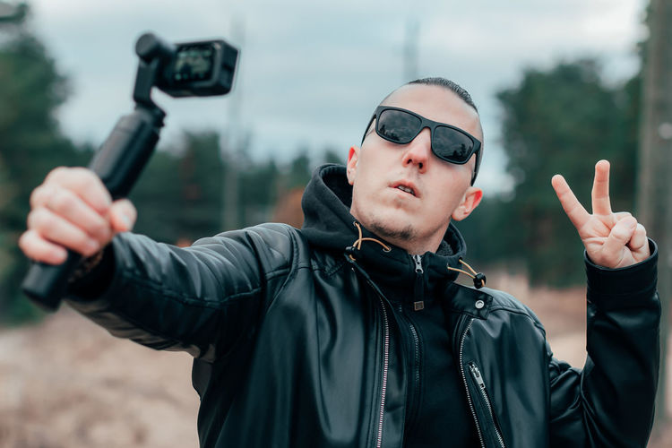 Young man wearing sunglasses filming with video camera