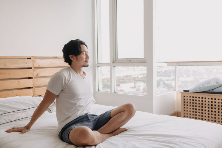 Side view of man sitting on bed