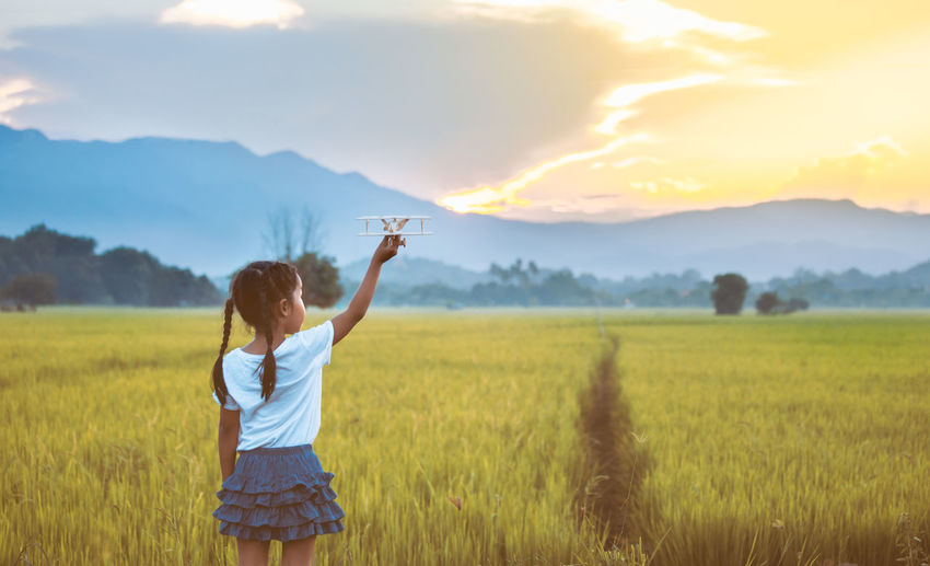 Cute asian child girl playing with toy wooden airplane in the field at sunset time in vintage color tone Asian  Field Freedom Fun Happy Imagination Nature Plane Travel Airplane Aviator Child Cornfield Countryside Cute Daughter Enjoying Life Flight Girl Inspiration Kid Outdoors Pilot Playing Toy