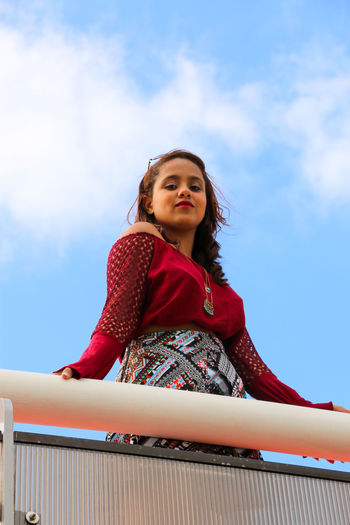 Low Angle Portrait Of Woman Standing At Railing Against Sky