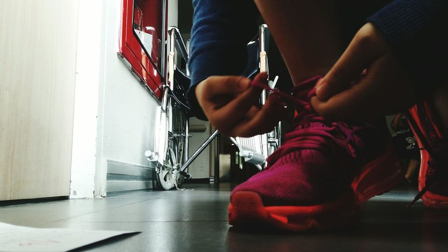 Low Section Of Man Tying Shoelace While Crouching On Floor