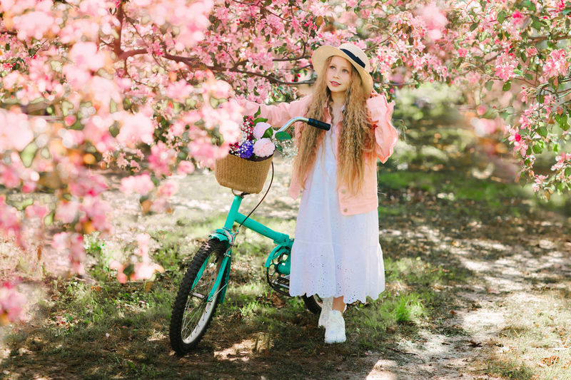 Cute girl with bicycle standing by flowering plant