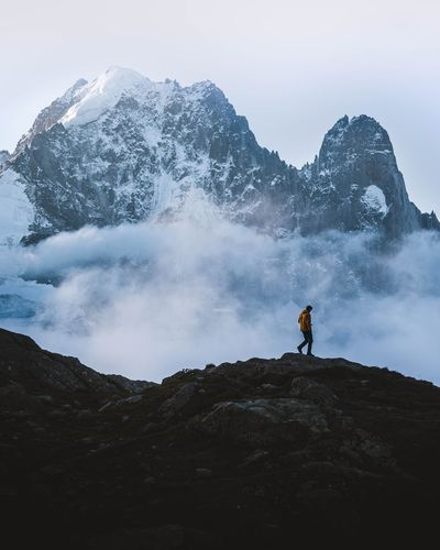Man on rock in mountains against sky