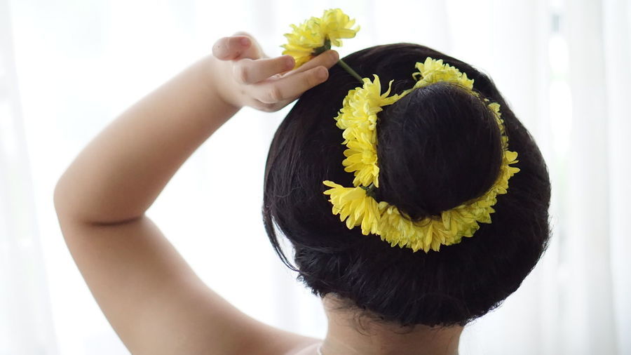 Midsection of woman holding yellow flower