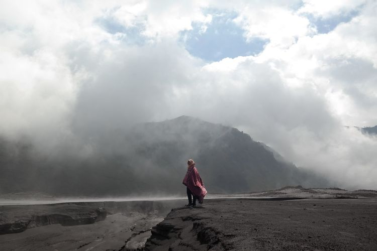 Girl wrapped in blanket standing against mountains during winter