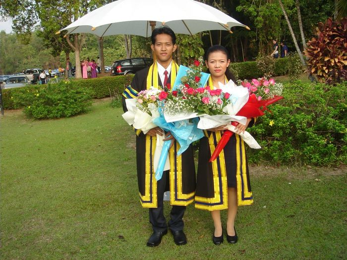 Portrait of smiling people holding bouquets wearing graduation gown standing at park