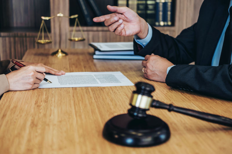 Midsection of judge gesturing while client signing contract on table
