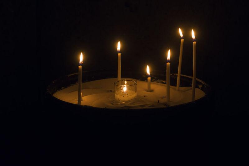 Close-up of illuminated candles in darkroom
