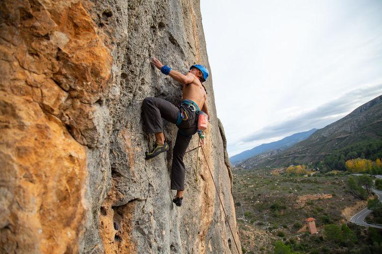 Shirtless Man Climbing Rock