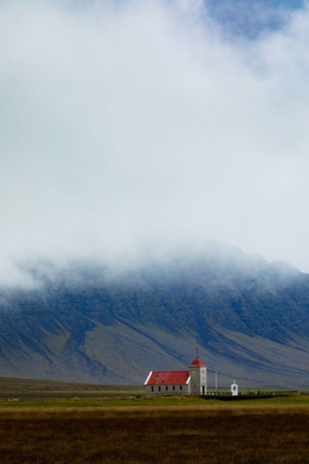 Small church building in fertile landscape before towering mountains mostly hidden in foggy clouds, Western Region of Iceland, IS, Europe Iceland Europe Eu Travel Trip Destination Building Chapel Church Clouds Foggy Weather Fogs Landscape Barren No People Outdoors Nature Environment Land Mountain Scenics - Nature Built Structure Architecture House Grass Building Exterior Rural Scene Agricultural Building Cloud - Sky The Architect - 2019 EyeEm Awards