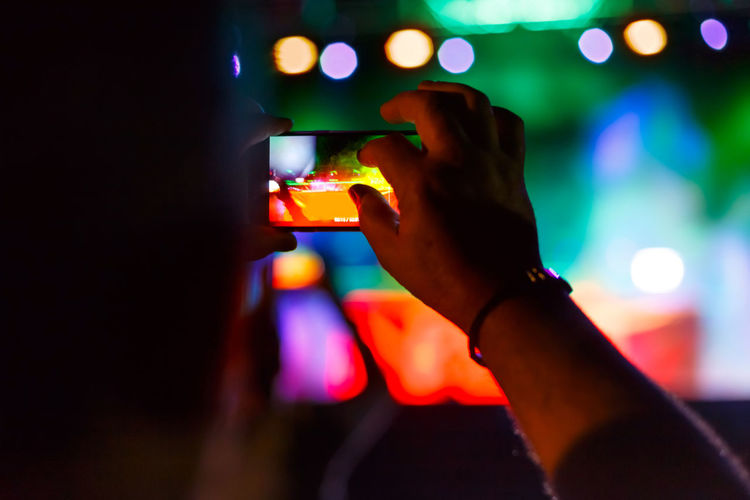 Man capturing a video on a mobile phone at a music festival. Event Fun Live Music Music Show Silhouette Social Stage Concert Crowd Digital Entertainment Festival Hand Holding Mobile Night Nightlife Party People Performance Phone Smartphone Video Young Adult