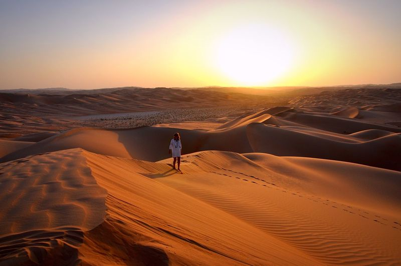 Woman walking on desert against sky during sunset